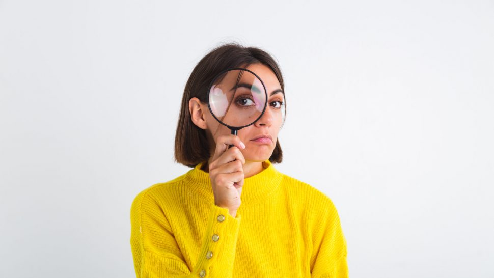 Pretty woman in yellow sweater on white background held magnifier happy positive playful