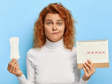 Puzzled ginger woman holds sanitary napkin and menstruation calendar with marked red days, suffers from period cramps, controls her women health, has periods this week, poses over blue background