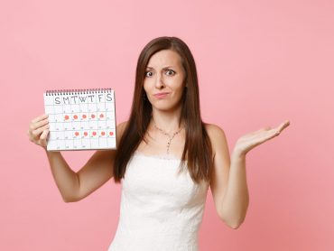 Puzzled guilty bride woman in wedding dress spread hand hold female periods calendar for checking menstruation days isolated on pink background. Medical, healthcare, gynecological concept. Copy space