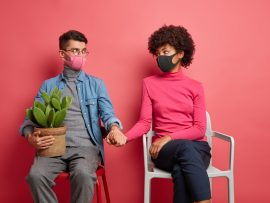 Serious husband and wife infected with coronavirus support each other hold hands wear protective face masks sit on chairs wear casual clothing spend time at home isolated over pink background