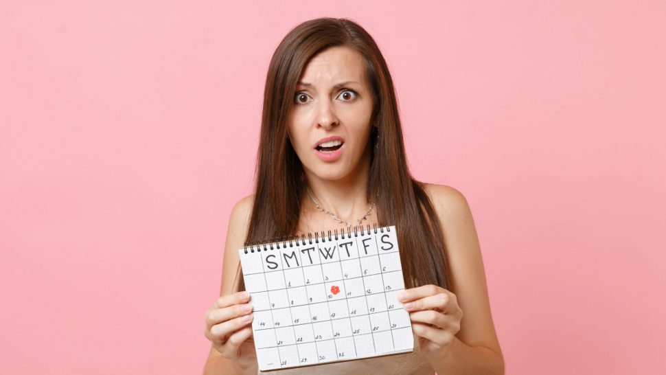 Shocked concerned bride woman in white wedding dress holding female periods calendar for checking menstruation days isolated on pink background. Medical, healthcare, gynecological concept. Copy space